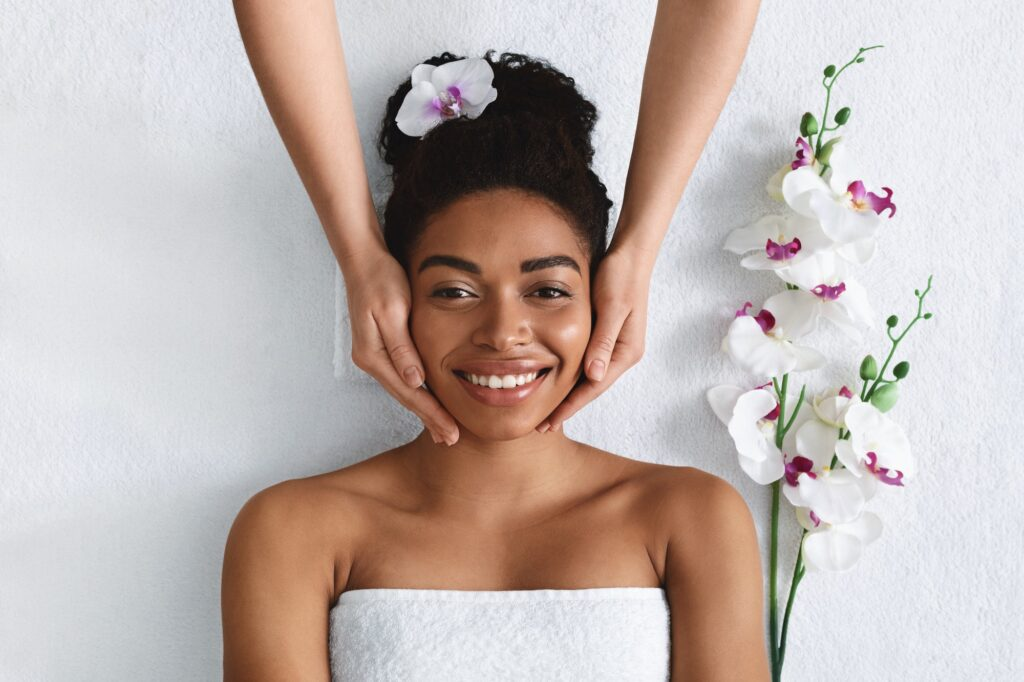 Beautician making face massage for happy black lady